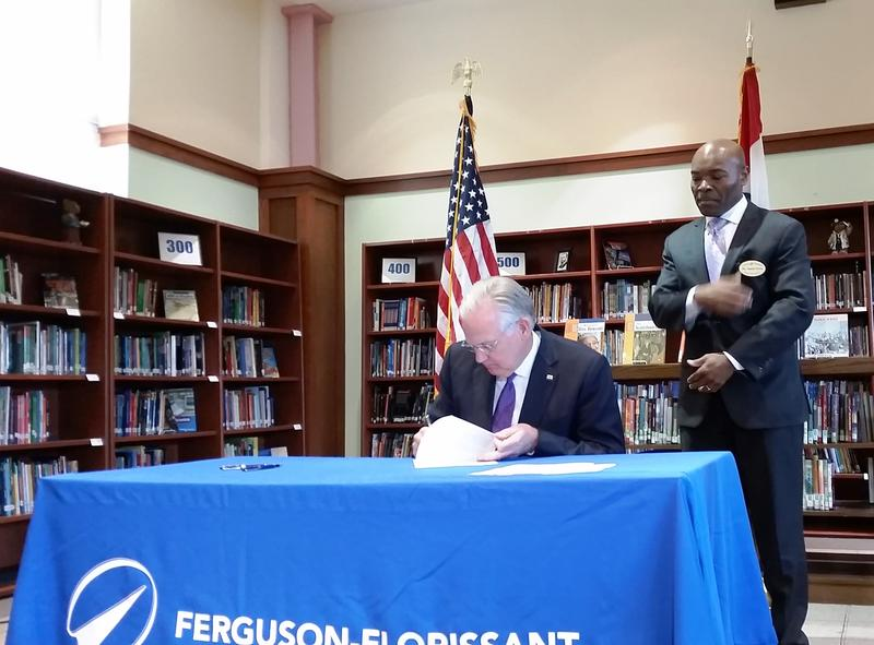 Ferguson-Florissant schools superintendent Joseph Davis watches as Gov. Jay Nixon vetoes a measure that would have changed the state's school funding formula on May 4, 2016.