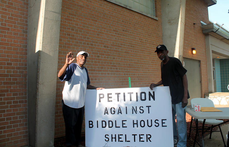 Carr Square residents Kevin Costello and Joseph Futrell gather petitions against Biddle House outside the public forum introducing the agencies that applied to run it on Wed. May, 25, 2016.