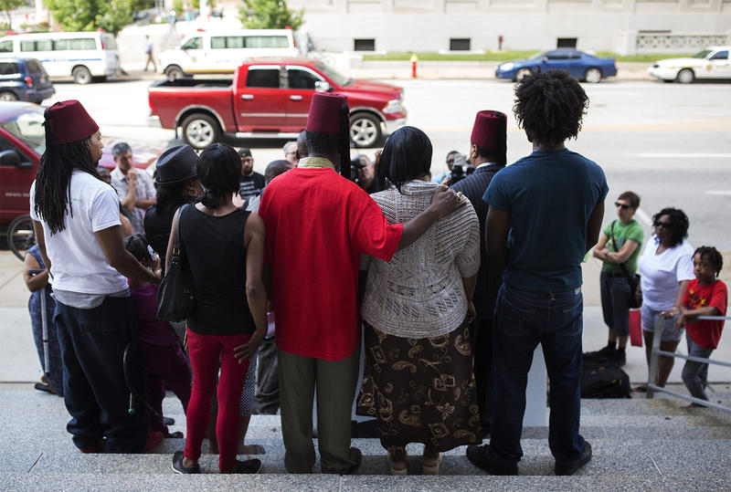 Relatives of Mansur Ball-Bey stand on the courthouse steps as attorneys speak to reporters on Thursday afternoon.