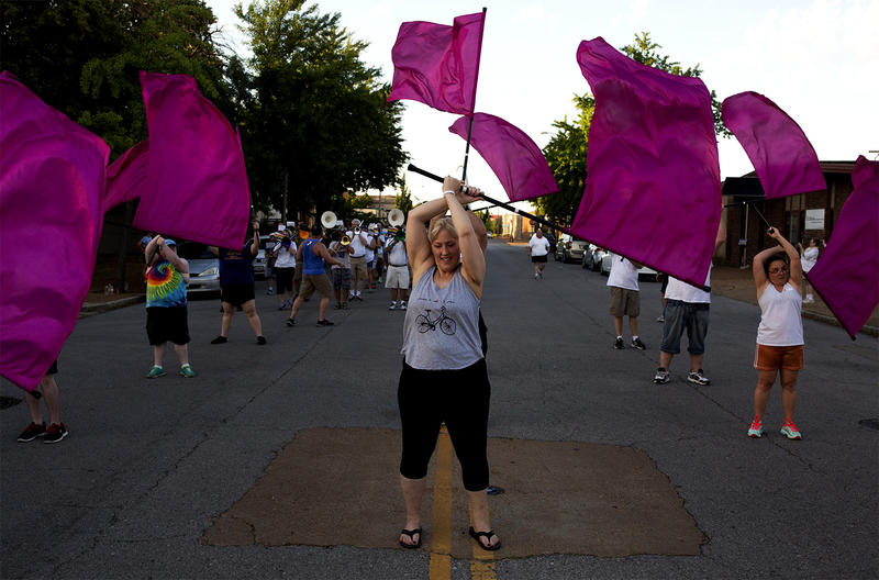 Stacey Crawford twirls flags with the color guard at a Band Together rehearsal.