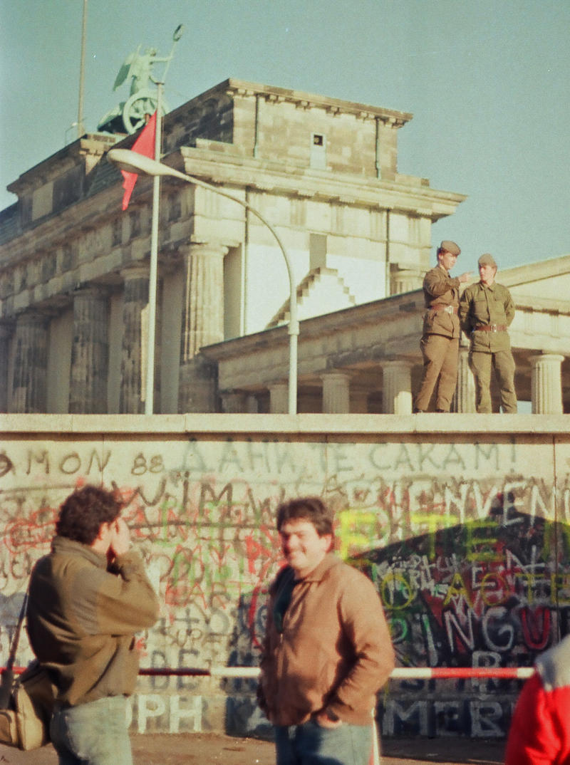 xxxRobert Koenig | Beacon staff From the west, two West Germans gather at Wall, while East German police stand guard on top of it. From Nov. 1989.