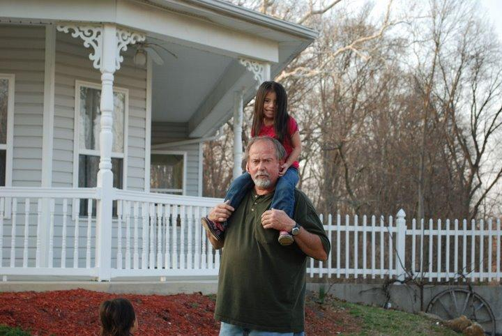 Rick Hoffman carries one of his granddaughters outside his home.