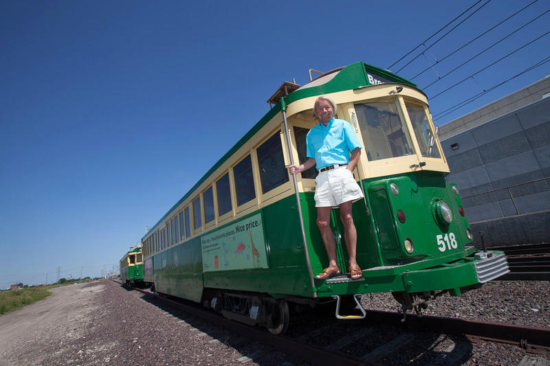 Joe Edwards poses with a trolley car purchased in Seattle for the Loop Trolley.