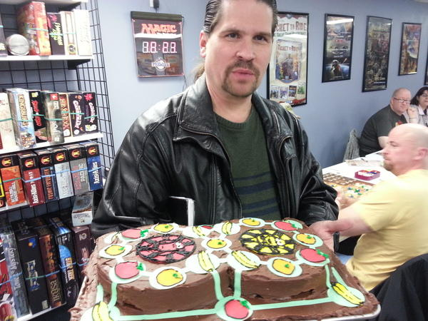 Mark Sellmeyer with a celebratory Spin Monkey cake on the eighth anniversary of the St. Louis Board Game Meet-Up Group.