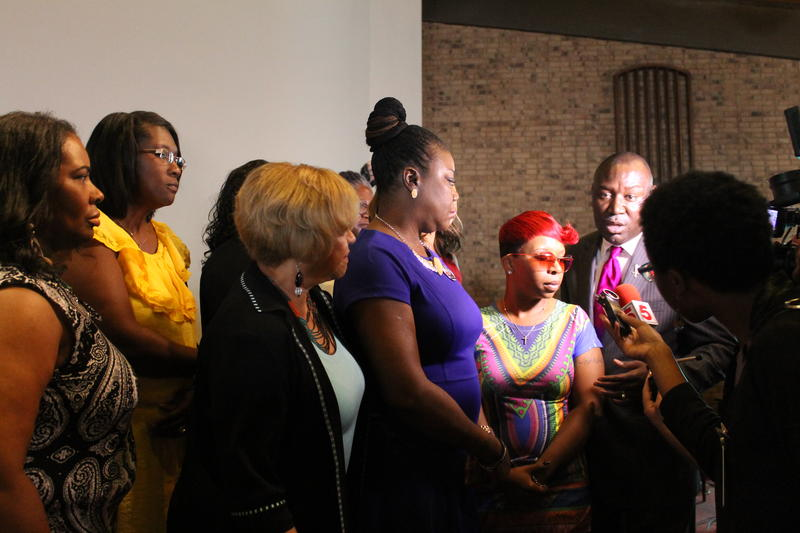 Group of women speak to reporters under the spotlight of a video camera.