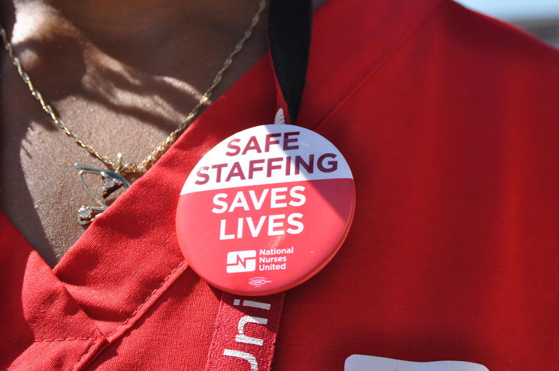 Marchelle Vernell-Bettis, a trauma ICU nurse, wears a button during an informational picket for St. Louis University Hospital's nurses union.