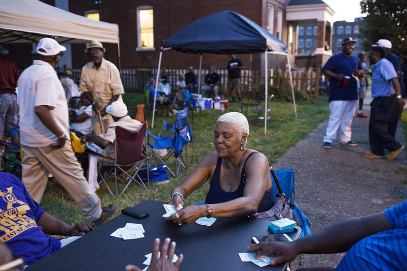 Brenda Nelson plays a card game with friends on Mullanphy Street during the street's last annual block party on Saturday.