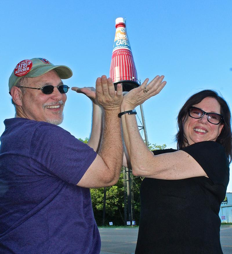Mike Gassmann and Judy DeMoisy stike a pose that's popular with visitors to the World's Largest Catsup Bottle in Collinsville. They organize the water tower's annual festival.