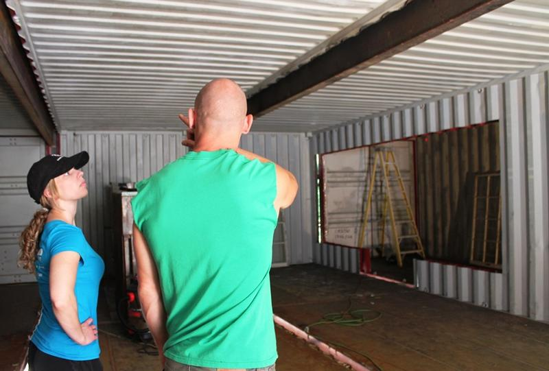 Brie and Zack Smithey inside their container home. Most of the inside walls have been removed.