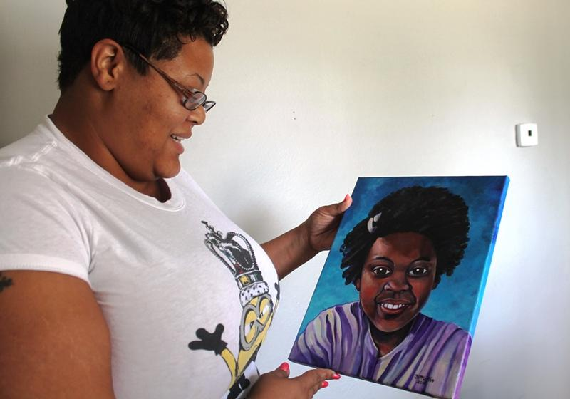 Kenrich Henderson gazes at a portrait of her daughter Jamyla Bolden. The painting is a gift from St. Louis artist Jane Martin and an organization called Faces Not Forgotten that produces portraits of children killed by gun violence.