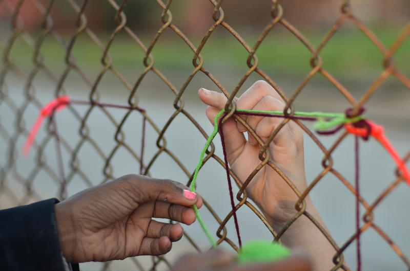 Two child hands pass red and green string through a fence