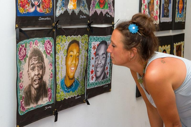 Sara McGibony studies a portrait on display at the Jacoby Arts Center in Alton.
