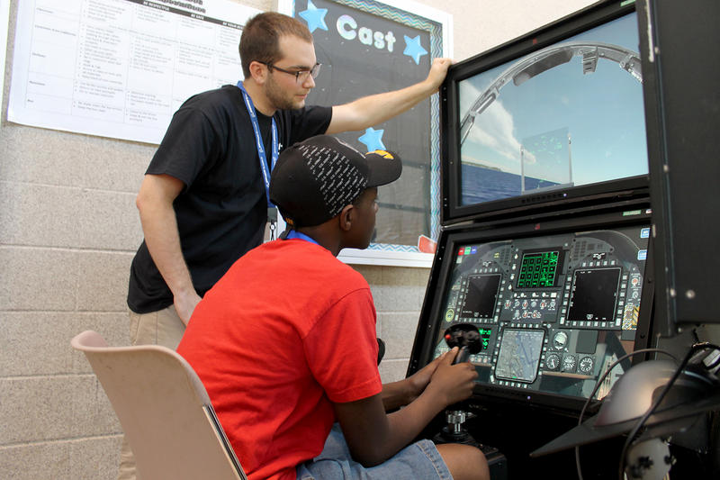 Boeing volunteer Levi Heilman helps Berkley Middle Schooler Xavier Higgs navigate a flight simulator Saturday, July 16, 2016.