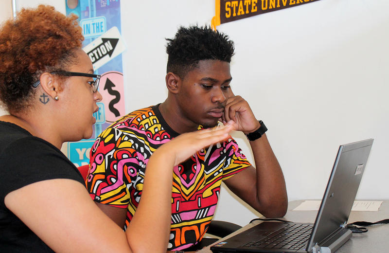 Danielle Washington of the Wyman Center walks Ozzie Furlow through financial aid literacy training at St. Louis Graduates' High School to College Center. Furlow plans to enroll as a freshman at Arkansas Baptist in August 2016.