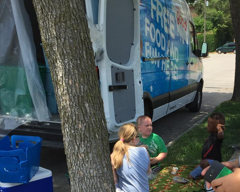 Local children eat the meal they got from Operation Food Search's mobile food truck. The free meal program makes sure kids who rely on free and reduced-price school meals get food during the summer months.