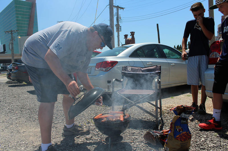 Jim Schroeder checks the grill outside the dome where the St. Louis Rams used to play. He tailgated with family and friends Saturday, July 23, 2016 before going to an exhibition game played by members of the 1999 championship team.
