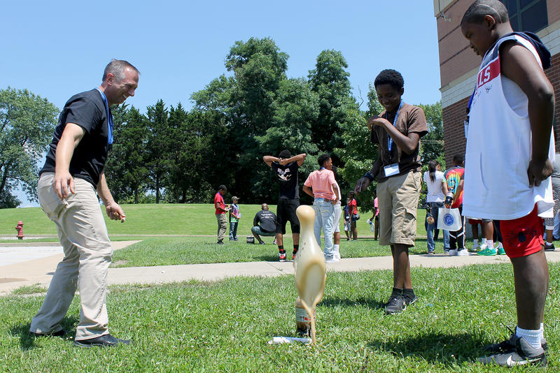 Tim Sayers of Boeing helps 8th grader Nathan Washington put Mentos in diet coke to watch the drink shoot in the air.