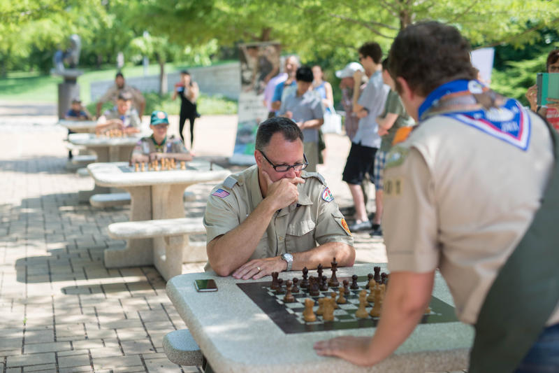 Kayden Troff, standing, plays chess in Forest Park.