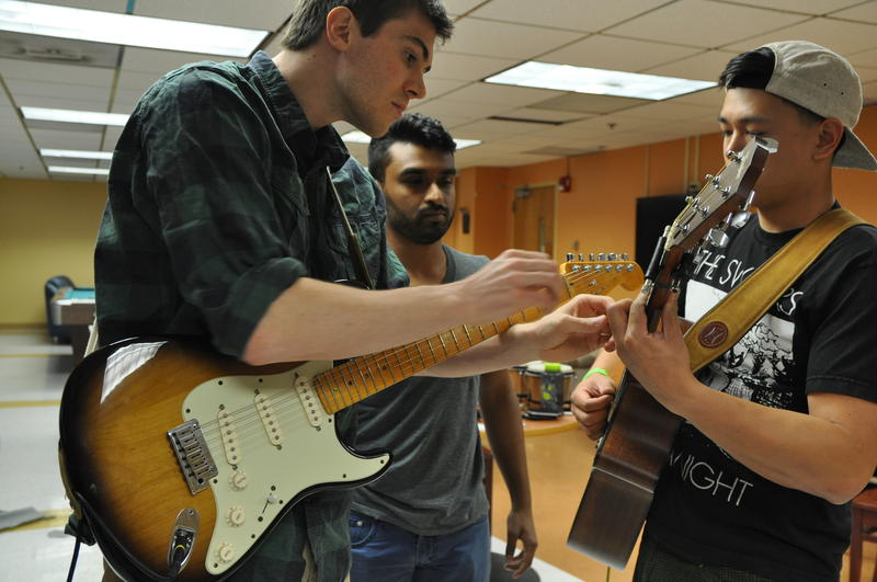 "Members of ""The Palpations,"" a band started by second-year medical students, try to fix a broken guitar string during practice."