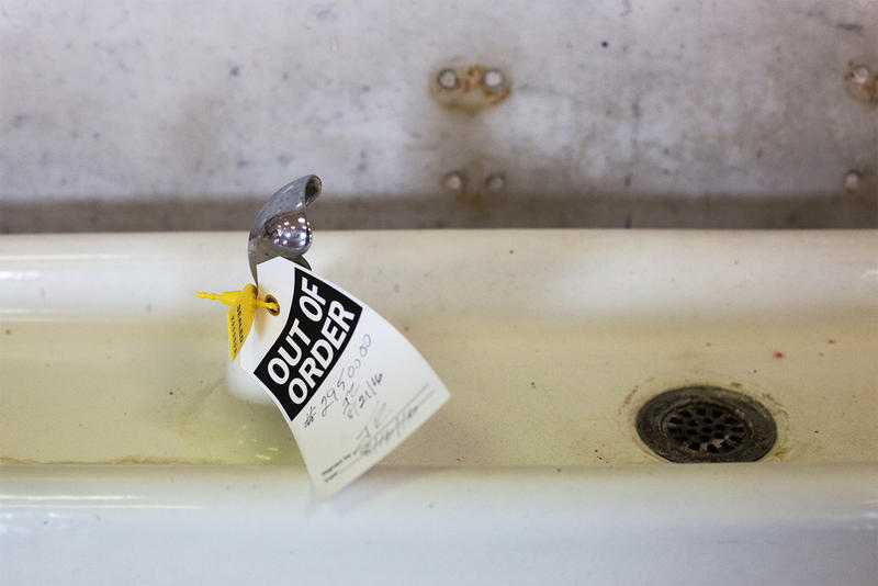 "An ""out of order"" sign hangs from the pipes of a water fountain at Patrick Henry Elementary School in St. Louis."