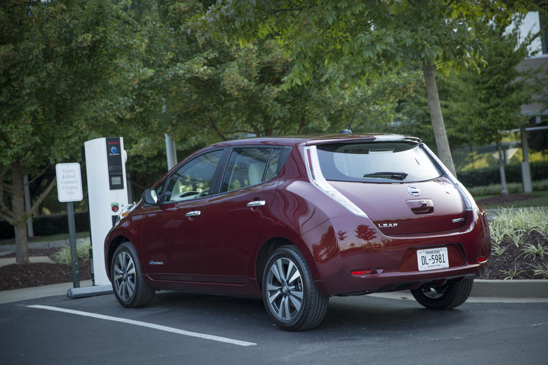 A Nissan Leaf getting charged up in a parking lot.