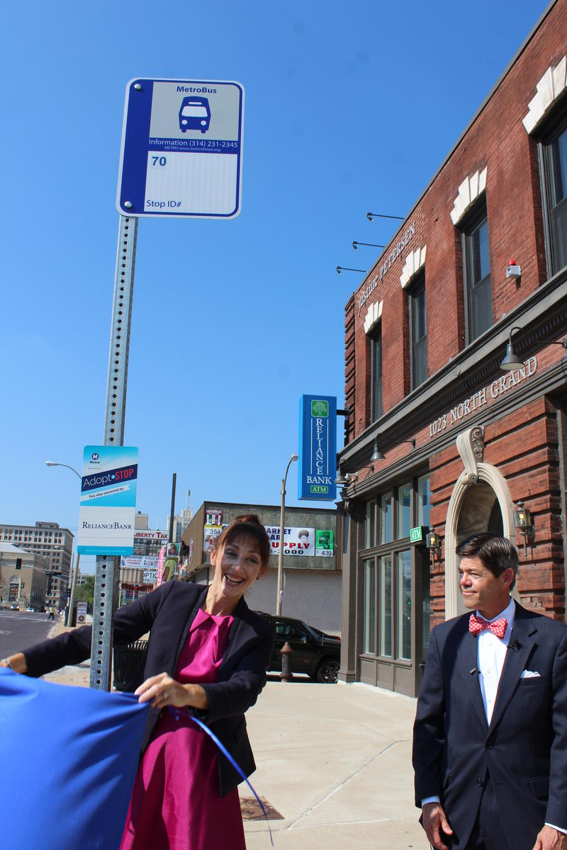 Metro Transit's Jessica Mefford-Miller and Reliance Bank's Allan Ivie IV unveil the Adopt-a-Stop signage. The bank is committed to cleaning the bus stop regularly for one year.