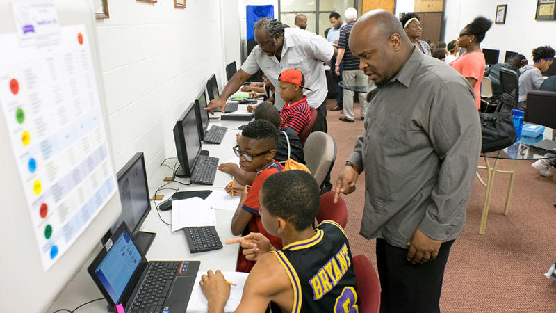 UMSL grad students Aaron Willis, right, and Mario Charles help students in the ULEAD program.