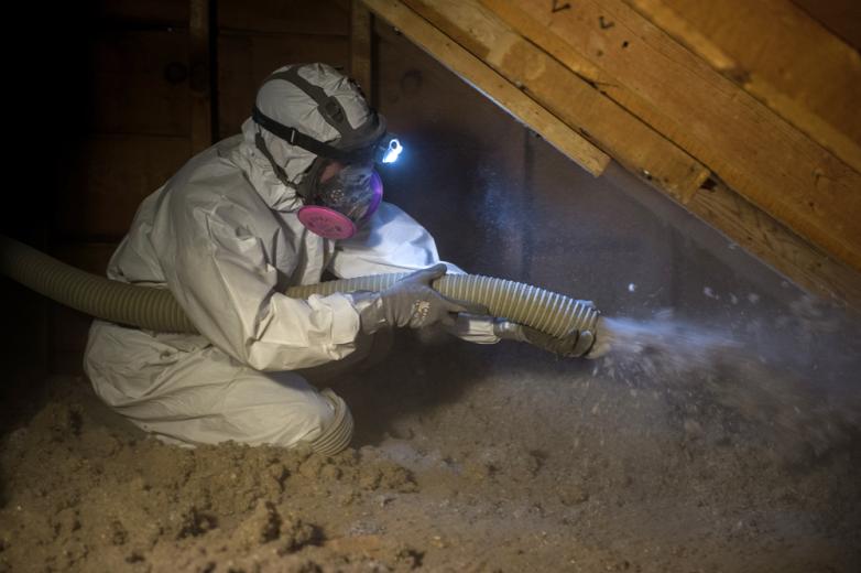 A worker installs fiberglass insulation.