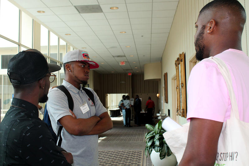 Montrelle Day of the East St. Louis health outreach organization WPT talks with othet attendees at the St. Louis forum on Aug. 20, 2016.
