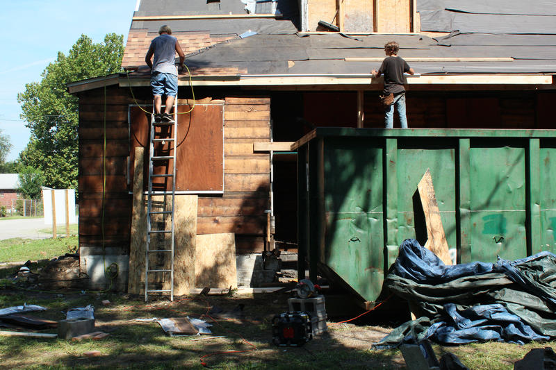 Roofers attach new shingles to the delapidated roof of Miles Davis' childhood home.