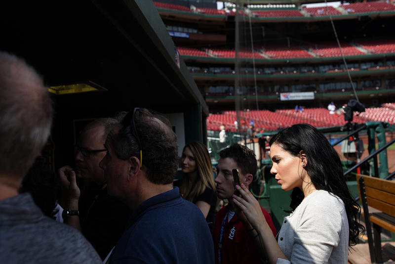 Alexandra Noboa takes pictures for social media as reporters conduct a pre-game interview at Busch Stadium. Noboa, the Cardinals' Spanish translator, launched the @cardenales Twitter account.
