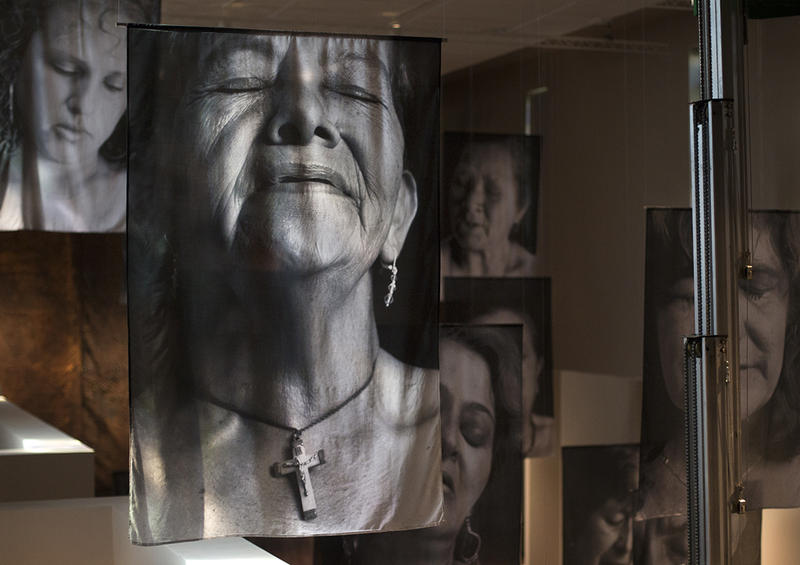 Portraits hang at the Museum of Contemporary Religious Art as workers finish setting up Erika Diettes' exhibit.