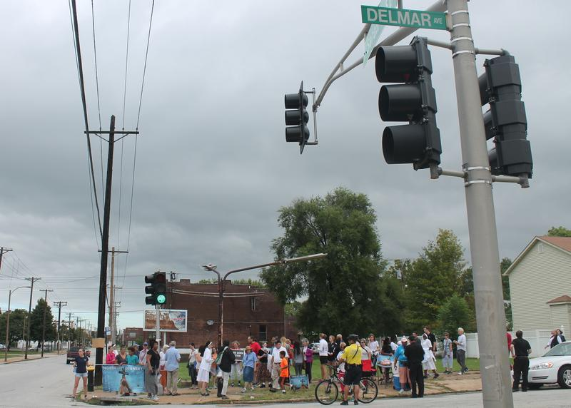 St. Louis area Catholics and other residents pause to pray at the corner of Delmar Boulevard and Sarah Street in St. Louis, during the Crossing the Delmar Divide pilgrimage.