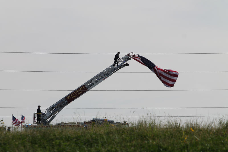 West County Fire raises a massive American flag on the ladder of a fire truck along the route to Officer Snyder's grave.