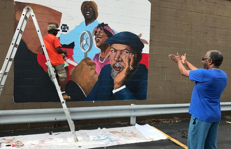 Artist William Burton Jr. talks with Black Rep founder Ron Himes as he works on a mural on the side of the theater company's office building on October 31, 2016.