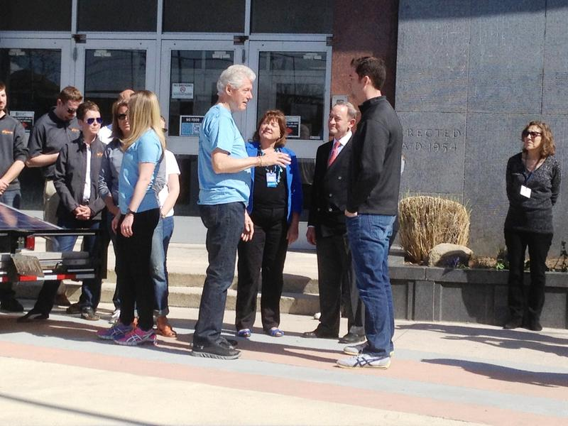 Former President Bill Clinton chats with volunteers at Gateway STEM High School in St. Louis.