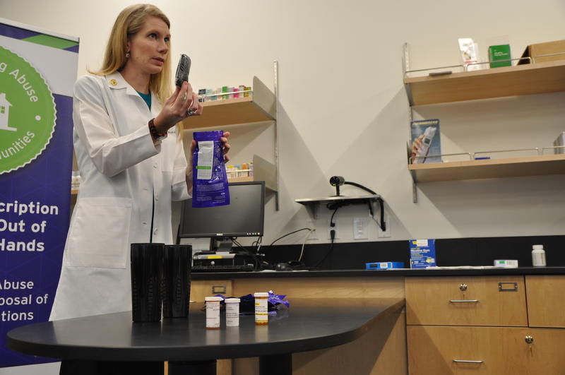 St. Louis College of Pharmacy professor Amy Tiemeier demonstrates how to use a medication disposal pouch to promote National Prescription Drug Take-Back Day. (Oct. 20, 2016)