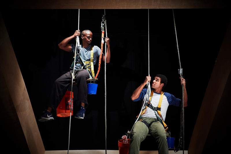 "Two immigrant men hang suspended in the air as window washers in the play ""Spended"""