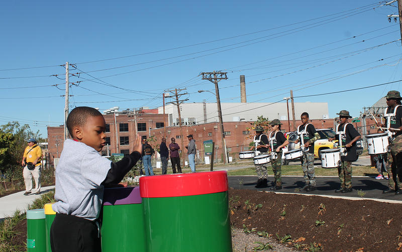 Brandon Rigmaiden, nephew of Wellston Mayor Nathaniel Griffin, plays with the musical installation at Trojan Park, mirroring the actions of the drum line performing in celebration of the park's opening day.