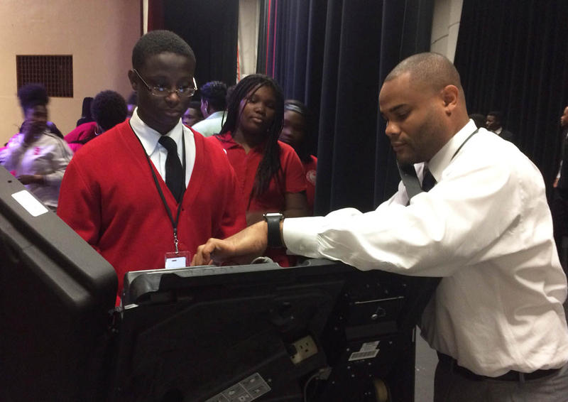 students try out a voting machine in Jennings