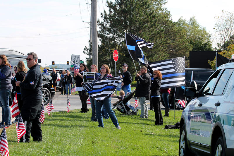 Law enforcement supporters greet Officer Snyder's funeral procession with signs and blue, black and white flags.