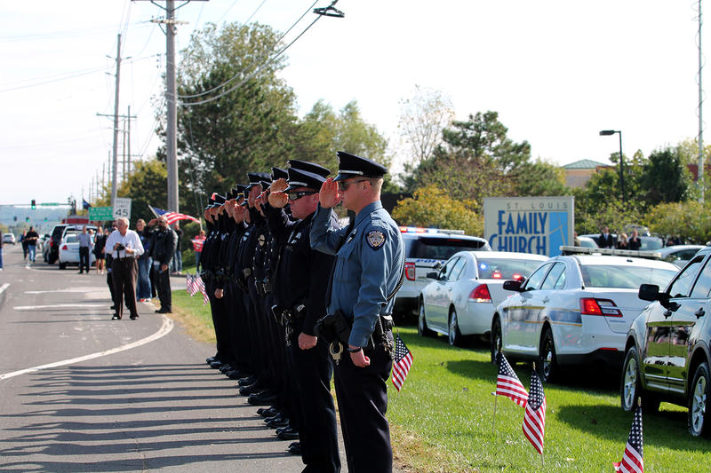 Police officers from several St. Louis area departments salute Officer Blake Snyder's funeral procession as it arrives at St. Louis Family Church in Chesterfield on Thursday, Oct. 13, 2016.