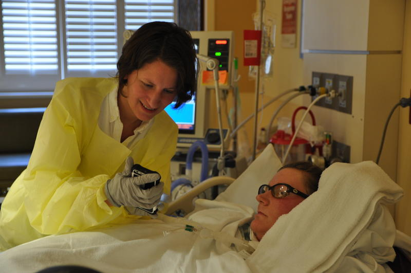 Tara Hegger, right, looks through pictures with her cousin, Lisa Pepper. Hegger has stayed in Mercy Hospital's intensive care unit for three months, because she can't find a nursing home in the state of Missouri that will accept her.