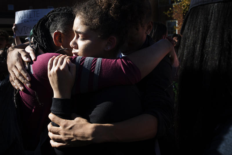 Friends comfort each other outside Ladue Horton Watkins High School as students gather to support the mother of a student who was burned with a hot glue gun.