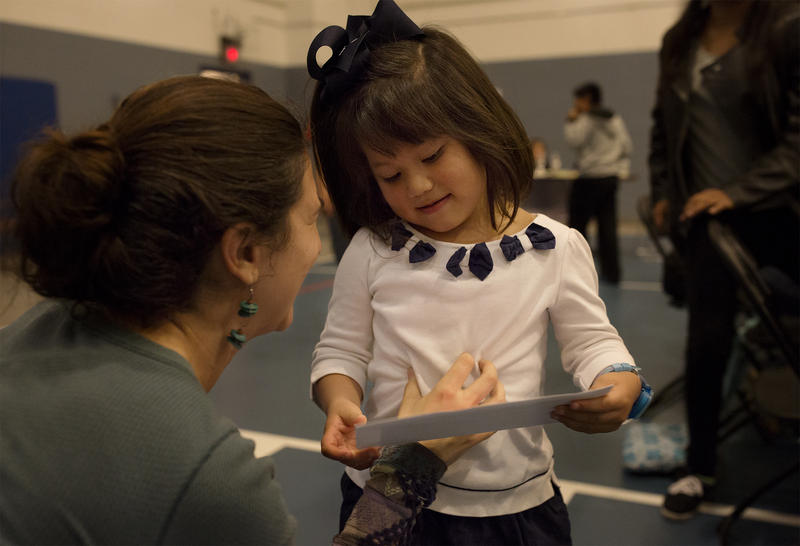 Miley, age 4, whose mother is undocumented, receives a letter of support and encouragement during a community dinner at Kingdom House on Nov. 17, 2016.