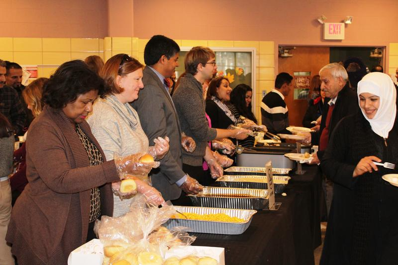 International Institute staff and volunteers serve a Thanksgiving meal to new refugees and immigrants to the St. Louis area on Tuesday, Nov. 22, 2016.