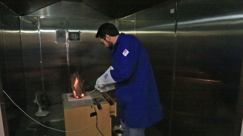 A member of Washington University engineering professor Rajan Chakrabarty's laboratory lights up forest material in a combustion chamber.