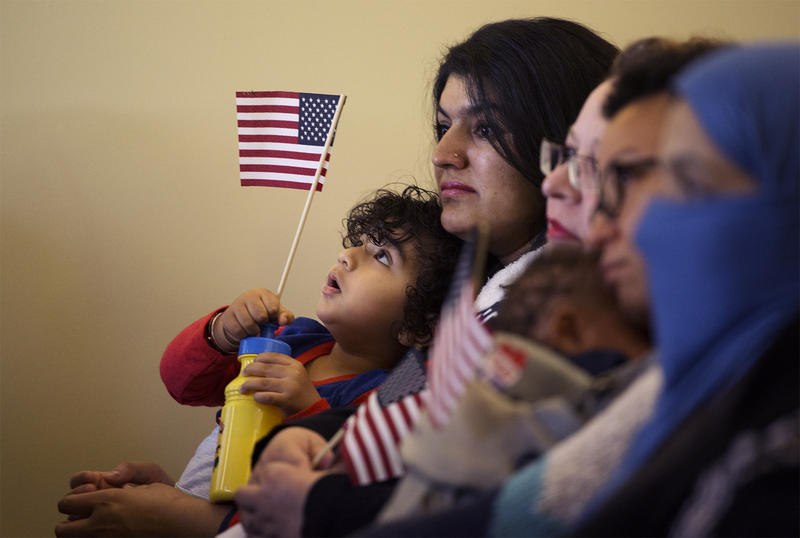 Arjun Sidhu holds an American flag while sitting with his mother, Mandeep Sidhu, originally from India, at a naturalization ceremony held at Ulysses S. Grant National Historic Site on Nov. 10, 2016.
