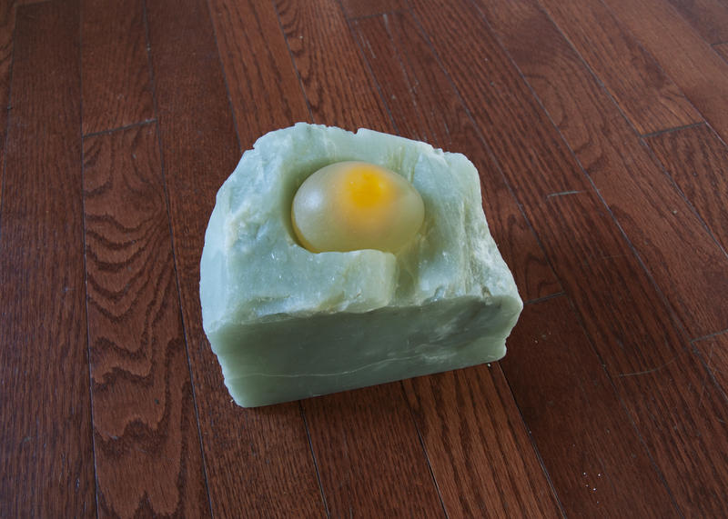 An uncooked egg sits in stone, the shell turned transluscent by white vinegar. Through it the yolk is visible.