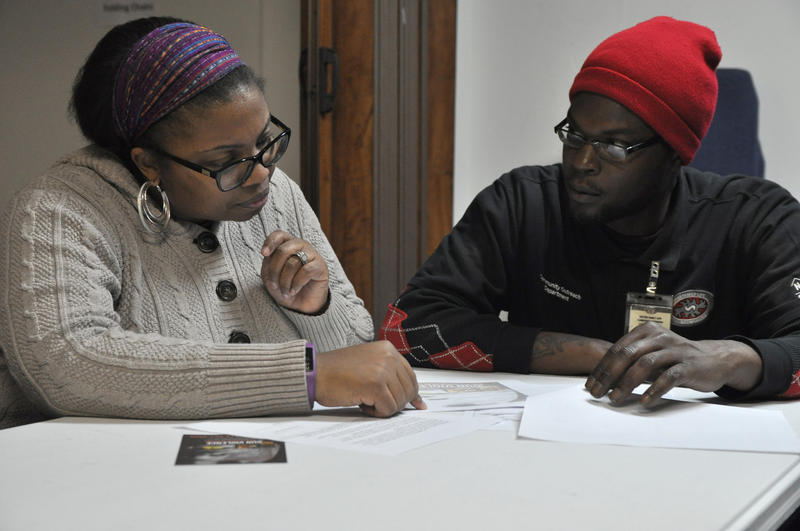 Volunteer counselors Dr. Marva Robinson, left, and Adrian Wrice discuss a case during drop-in hours in the basement of the New Northside Missionary Baptist Church.